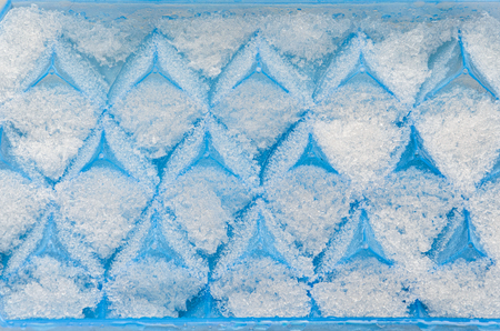 Texture of hoarfrost on a blue tray for making ice cubes. Geometrical pattern with frost.