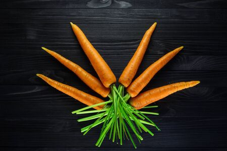Fresh carrots carefully laid out in a geometric pattern on a black wooden table top view