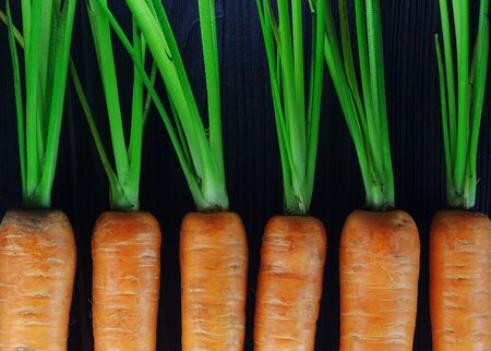 Fresh clean carrots densely packed near each other pattern on black background. Stock Photo