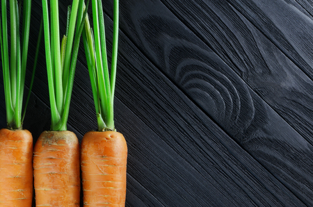 Fresh clean carrots on black wood background with a blank space for text top view Stock Photo