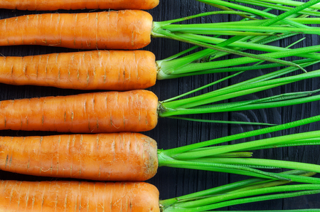 reiteration: Fresh carrots densely packed near each other pattern on black wood background top view