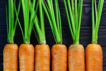 Fresh carrots densely packed near each other pattern on black wood background top view