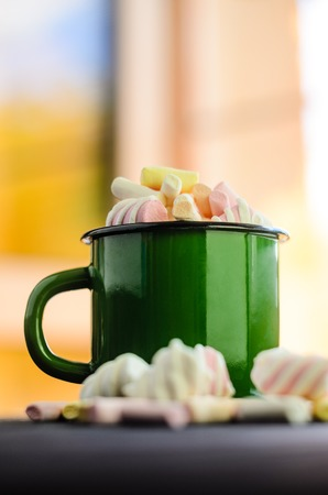 The green enameled mug is filled with a multicolored marshmallow on a black wooden table with blurred interior background close-up