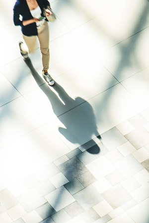 Silhouette of a walking woman with long shadow in a public building hall top view Stok Fotoğraf