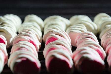 spongy: White and pink marshmallows neatly laid out on a black wooden table. Fresh and sweet marshmallows background