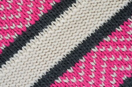 Texture of a beige knitted sweater close-up. Three-color pattern knitted winter sweater Stock Photo