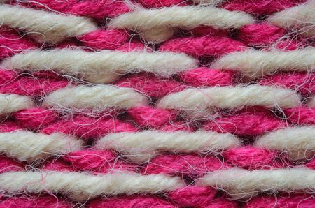 Texture of a beige and red knitted sweater close-up. Abstract pattern of winter sweater