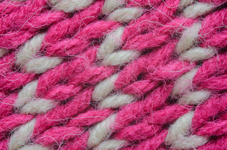 Texture of a beige and red knitted sweater close-up. Abstract pattern on winter knitted clothes