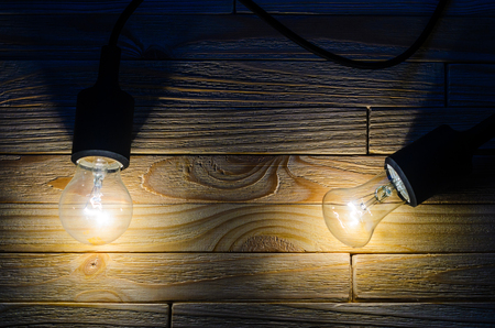 Two burning incandescent bulbs on a wooden background. A layout with an empty space for your text Imagens