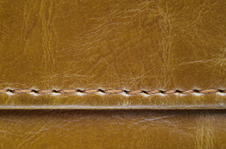 leather texture: Texture of brown leather with stitches. Element of leather clothing close-up. Seams on leather products