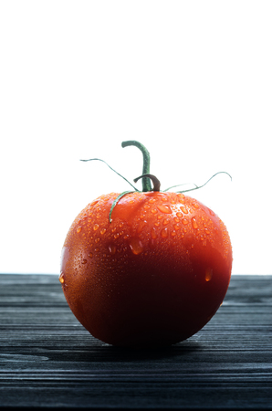 front desk: One Red Tomato on a Black Wooden Table Against White Background Close-Up