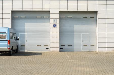 두 개의 회색 차고 문 및 주차 된 미니 버스입니다. 작은 개인 문을 포함하여 대형 자동 차고 문 이상.