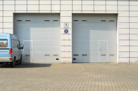 Twee grijze garagedeuren en een geparkeerde minibus. Grote automatische garagedeuren op en af met een kleinere persoonlijke deur.