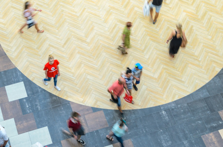 Silhouettes of Walking People in the Atrium of a Large Public Building, View from Above. Blur in Motion, Long Exposure. Abstract Background