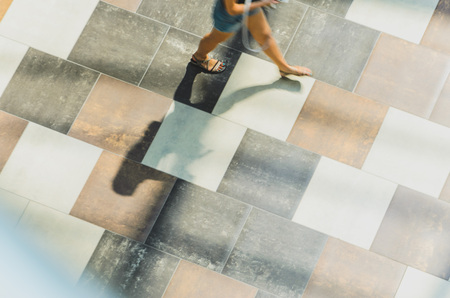 Silhouette of a walking woman with long shadow from above. Abstract background of blur in motion figure of a young woman in a public building hall top view. Blurred Abstract Background.