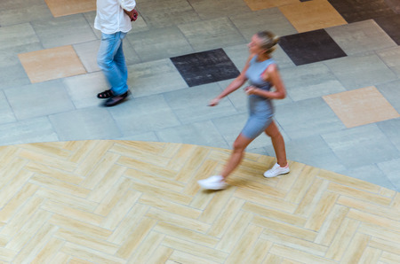 Silhouette of a walking woman, view from above. Abstract background of blur in motion figure of a young woman in a public building hall top view. Blurred Abstract Background. Stok Fotoğraf