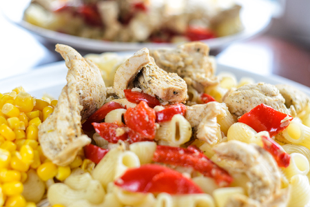 Hot Pasta with Chicken Breast Meat and Vegetables in Large White Plate on Wood Table, Close-Up. Food Background