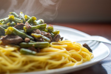 Steam from a Hot Dish with Delicious Pasta, Meat and Green Beans, Close-Up Stockfoto