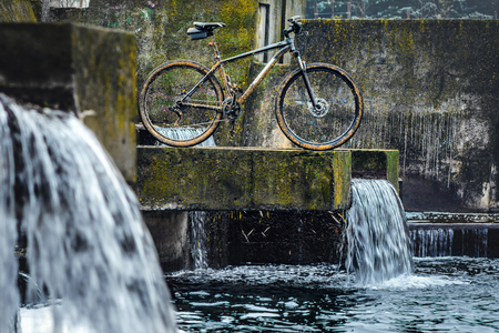 Dirty Mountain Bike Covered with Mud After Riding in Bad Weather Stands. Grey 29er Hardtail Bike on a Concrete Slab Against the Backdrop of an Urban Waterfall