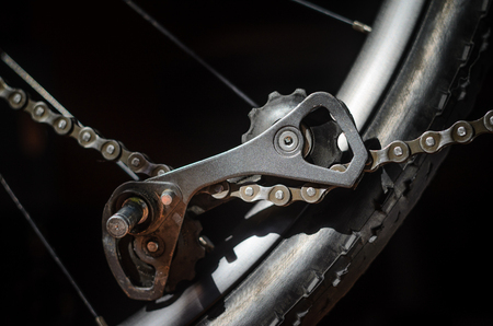 Rear Bicycle Derailleur Fell Apart in Half. Bicycle Rear Derailleur Foot is Detached from the Body. Unexpected Bike Failure. The Torn Off Derailleur Foot Hangs on Chain