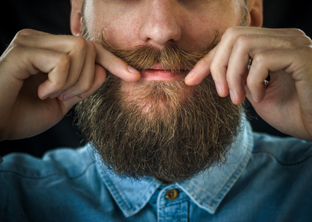 Bearded Man in a Blue Denim Shirt Twirling His Mustache with His Fingers. Portrait of a Hipster on Black Background Closeup