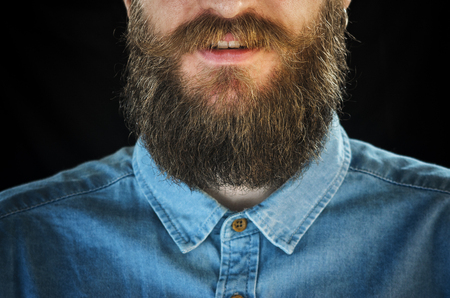 Portrait of Smiling Bearded Man in a Blue Denim Shirt on a Black Background. Hipster Look: Beard and Mustache Close-up