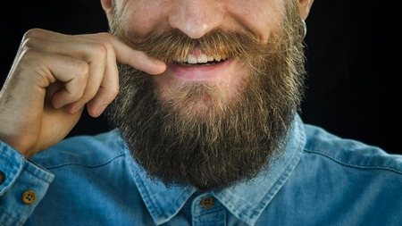 Smiling Bearded Man in a Blue Denim Shirt Twists the Mustache with His Hand on a Black Background. Hipster Look: Beard and Mustache Close-up