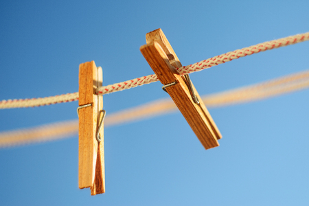 Two wooden clothespins on a clothesline against a blue sky background 版權商用圖片