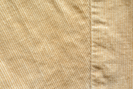 Texture of Beige Velvet Clothes with Stitches. Seams on Cloth. Textile Fabric of Corduroy as Background Standard-Bild