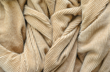 Texture of Soft Velvet Fabric with Folds Closeup. Texture of Beige Velvet Clothes. Textile Fabric of Corduroy as Background Stok Fotoğraf - 107168575