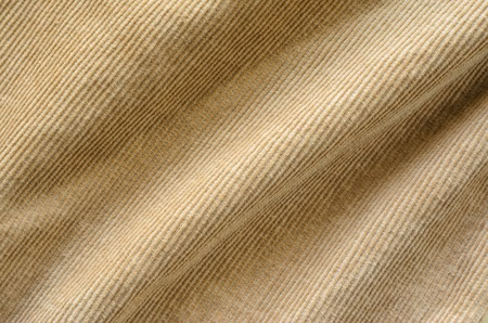 Texture of Soft Velvet Fabric with Folds Closeup. Texture of Beige Velvet Clothes. Textile Fabric of Corduroy as Background