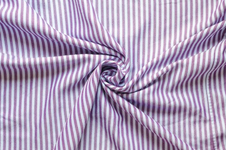 Crumpled striped fabric background. Textiles for shirts in lilac stripes. Twisted in the center cloth swatch Imagens