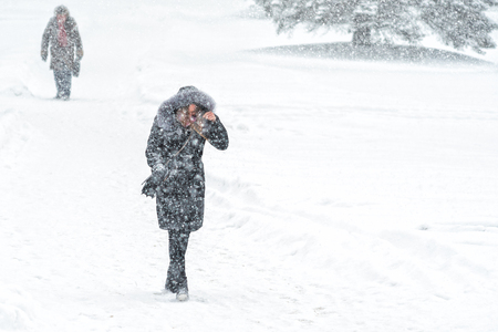 Young girl walk through snowfall resisting the pressure of a snowfall. Blizzard in an urban environment. Winter weather background Фото со стока