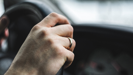 Men driver's hand with wedding ring on the steering wheel. Close up
