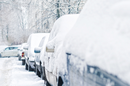 Cars in the parking lot are covered with a thick layer of snow. Concept: winter weather and car owner confrontation