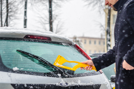 Young man in black coat cleans his car with yellow brush during snowfall. Winter inclement weather. Фото со стока