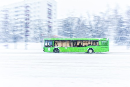 Green city bus rides a snowbound road during a snow storm. Abstract blur background. Concept of dangerous road conditions in winter