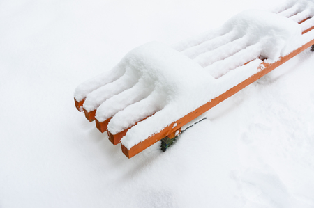 Orange color wood bench is covered with a thick layer of snow. Winter weather heavy snowfall concept. Top view. Empty blank background 스톡 콘텐츠