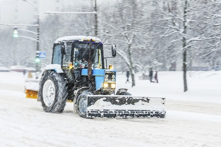 Blue snow plow tractor removes snow from the city road. Snowstorm in the city - seasonal abstract motion blur background