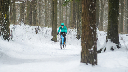 Cyclist on cyclocross bike trails in the snowy forest in winter. Downhill riding a snowy slope. Winter workout outdoors concept