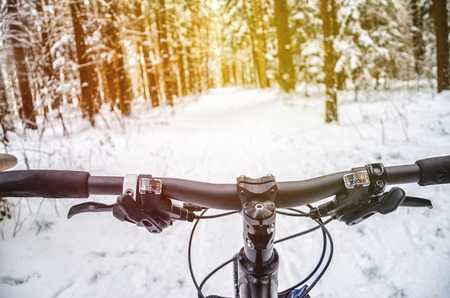 First-person view of cyclist in the winter forest. Wnter mountain bike concept