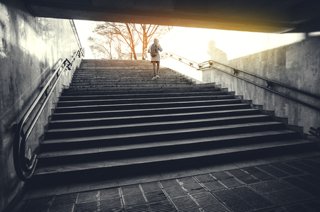 Tourist man in a hood with a large backpack climbs the stairs at dawn in an urban environment. Tourist in winter city concept Stok Fotoğraf