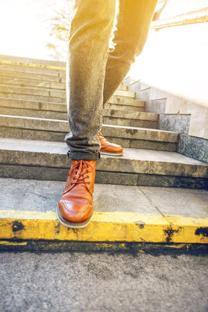 Man in beautiful brown leather shoes walks the granite stairs in an urban environment. Blank background. Life in motion concept Banque d'images - 113242894