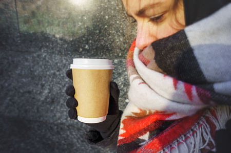 Young beautiful girl in gloves and in a large cozy scarf holding a paper cup of takeaway coffee. Paper cup layout for hot drinks background 版權商用圖片