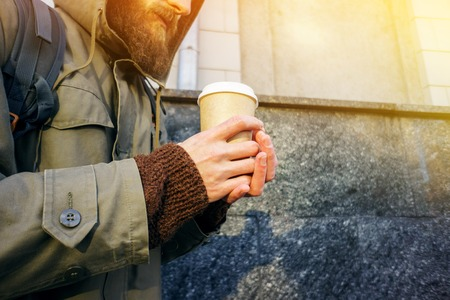 Paper cup of hot coffee in the hand of a bearded man in a jacket and a brown sweater. Warming drink in cold winter weather. Take away coffee concept. Coffee cup layout