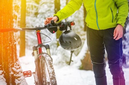 Male racer hangs helmet and gloves on the handlebars of a bicycle in snowy winter forest.. Break training for rest. Extreme sport background. Mountain bike safety concept.