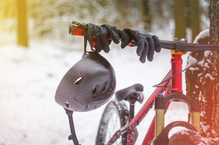 Black helmet with black sport gloves hangs on the handlebars of a bicycle in snowy winter forest. Mountain bike safety concept. Extreme sport background