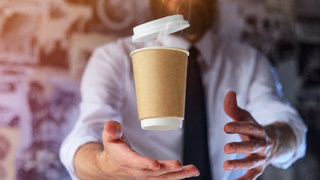 Barista in a white shirt with a tie holds floating in the air a paper cup with a hot drink on his outstretched arms. Barista wizard concept. Background for advertising and placing logo on your drink Foto de archivo