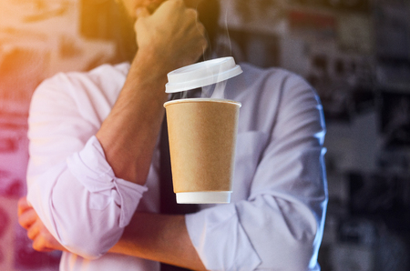 Meditative barista in a white shirt and tie and levitating paper cup of hot coffee. Background for advertising. Logo placement concept Stock Photo