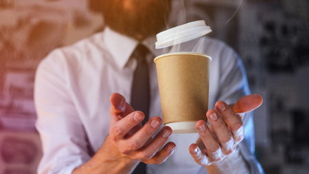 Barista in a white shirt with a tie holds floating in the air a paper cup with a hot drink on his outstretched arms. Barista wizard concept. Background for advertising and placing logo on your drink Stock Photo